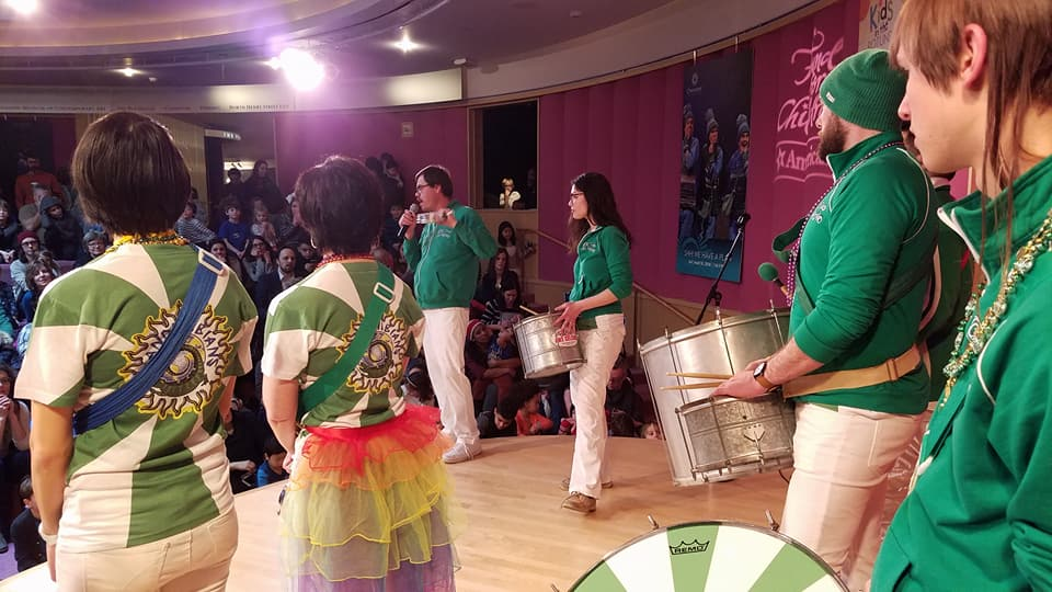 Drummers on Stage wearing green shirts